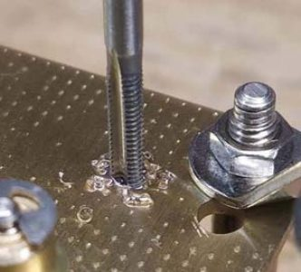Tapping a clock movement plate to take a screw